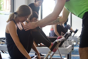 An instructor works with a client on a reformer