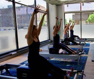 Pilates clients hold bars over their head while sitting on reformers
